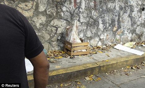 A police officer in Acapulco stands next to the sack containing five severed heads which has been placed in a small wooden crate photo