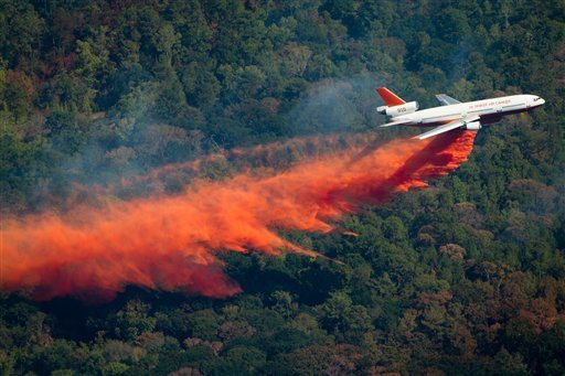 A DC-10 airplane drops retardant near Magnolia, Montgomery, Texas, to help fight a large wildfire almost like ones in Bastrop Texas (AP Photo/Houston Chronicle, Smiley N. Pool)