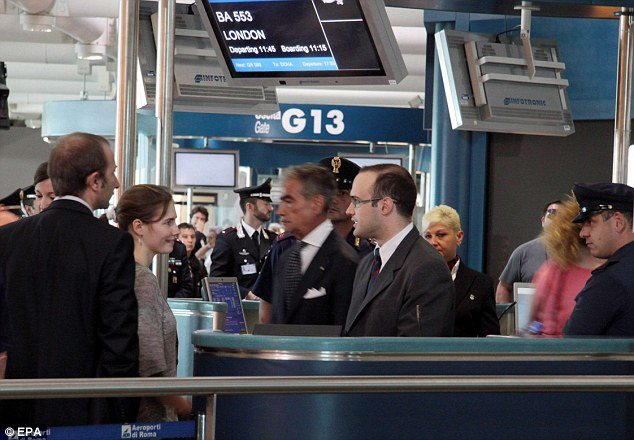 Amanda Knox talks to British Airways staff as she prepares to put baggage on to the flight
