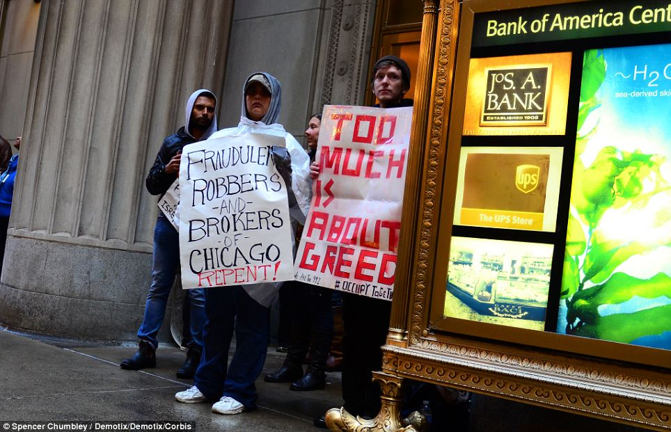 Demonstrators hold signs across from the Federal Reserve Bank of Chicago on Friday