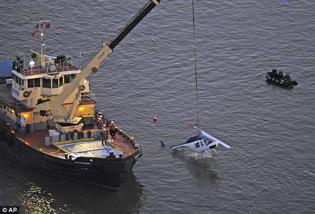 The Bell 206 tourist helicopter which was not equipped with floats was pulled from the East River hours after the crash photo