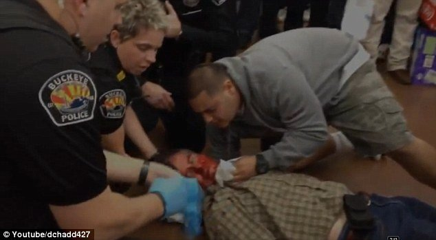 Jerald Allen Newman 54 is shown unconscious after an officer took him to the ground as cops are seen trying to sop up blood and outraged customers yell expletives photo