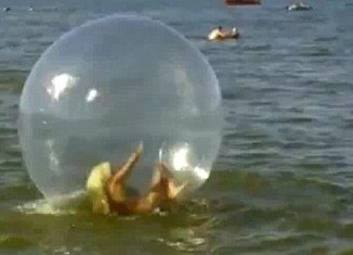 For two minutes the woman can be seen flapping about in the water sphere and even appears to head butt the soft side of the bubble, desperate to get back on her feet