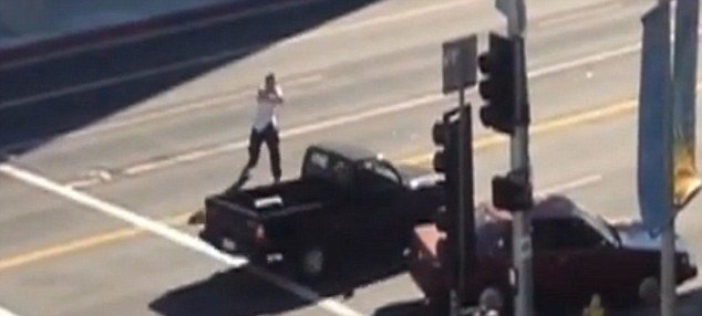 The shooter, a 26-year-old Hispanic dressed in a white sweat vest, was filmed from an office block standing in the middle of the road firing on pedestrians and motorists