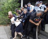 About 50 police escorted PM Julia Gillard and Tony Abbott from Canberra's Lobby restaurant after it was surrounded by some 200 supporters of the city's Aboriginal Tent Embassy