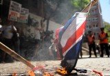 Around 100 left-wing activists have protested by burning Union flags outside the British embassy in Buenos Aires on Friday to demand Argentina break off diplomatic relations with the UK over the Falkland Islands dispute