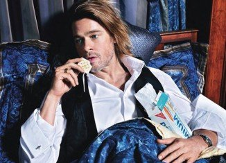 Inside W magazine Brad Pitt can be seen lying in bed under plush blue sheets, eating biscuits