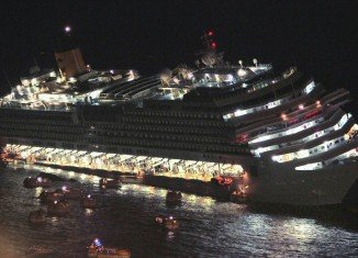Like a Titanic scene, lifeboats can be seen spilling from the sides of the ship into the gloomy waters off the island of Giglio as Costa Concordia cruise liner sinks into the sea