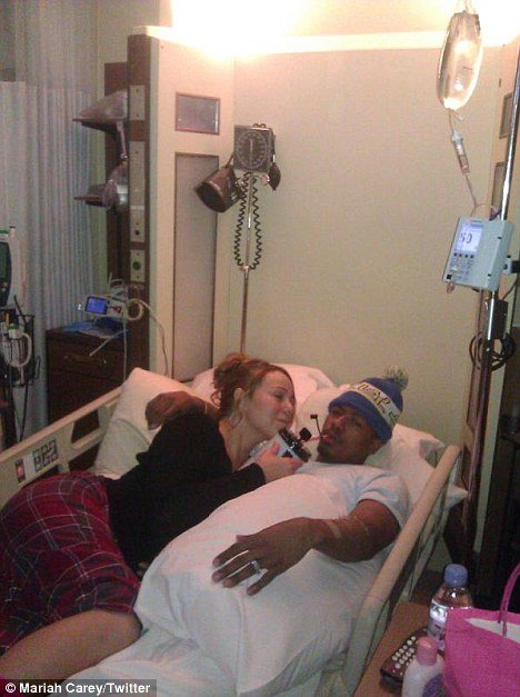 Mariah Carey, 41, bizarrely posted a photo of herself posing beside an ailing Nick Cannon, 31, in his hospital bed