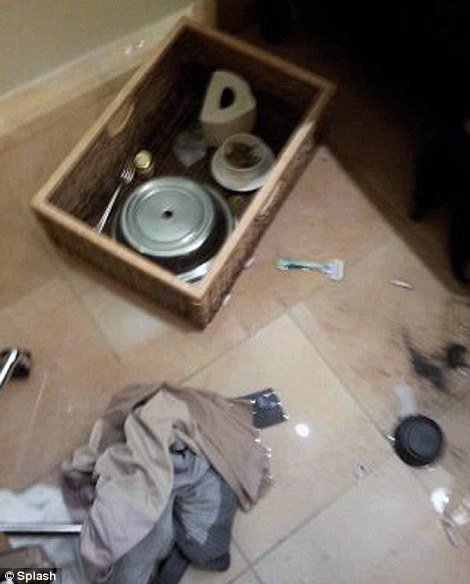 A tray can be seen on the floor of the hotel bathroom which is said to have contained a turkey sandwich and jalapenos, a Gilette razor, glass of water and items of clothing are also strewn on the floor