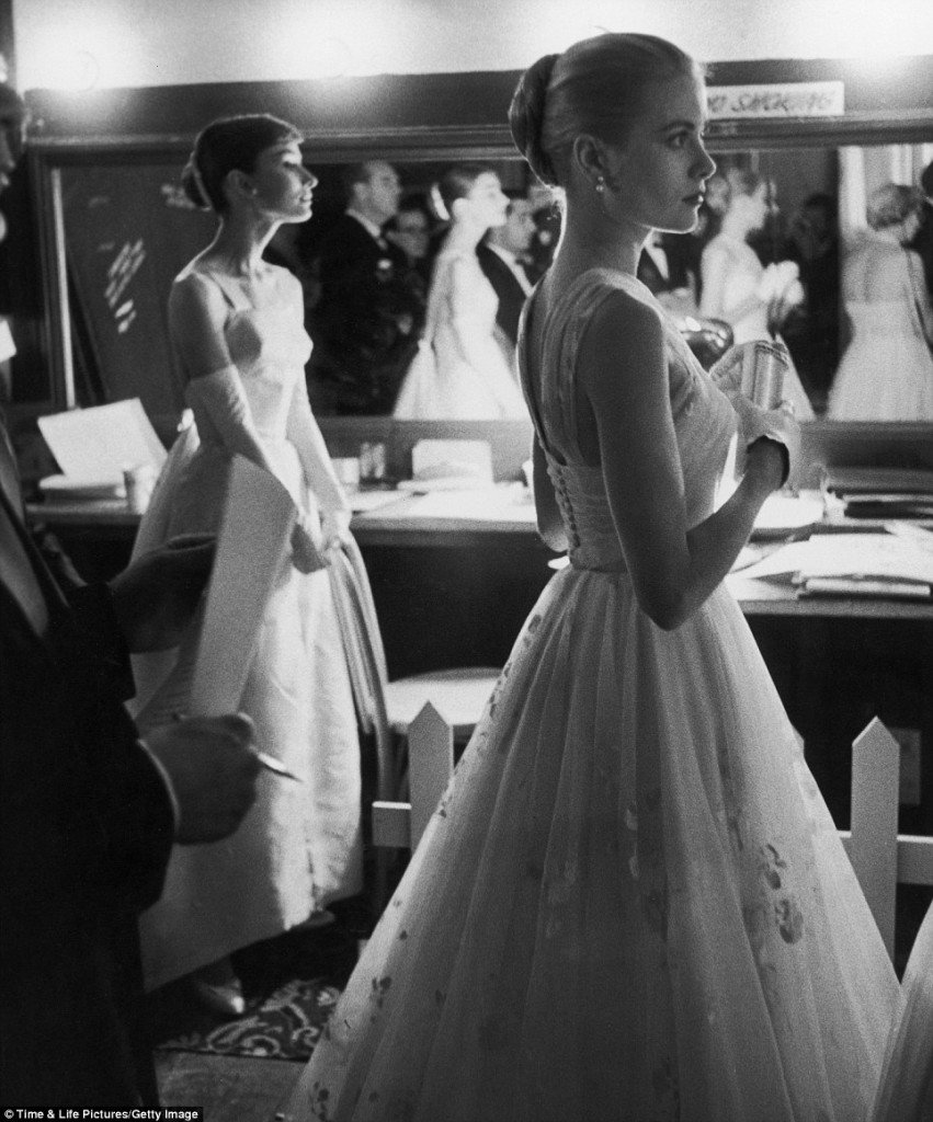 Audrey Hepburn and Grace Kelly wait with apparent nerves backstage to present an award