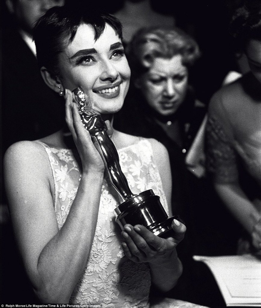 Audrey Hepburn grins and sports an elfin haircut while clutching her Oscar in 1953, for her breakout role in Roman Holiday alongside Gregory Peck