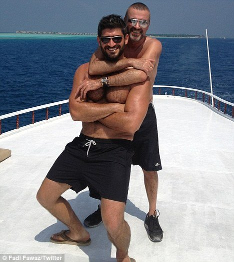 George Michael is seen smiling widely while hugging Fadi Fawaz who is also beaming with delight photo