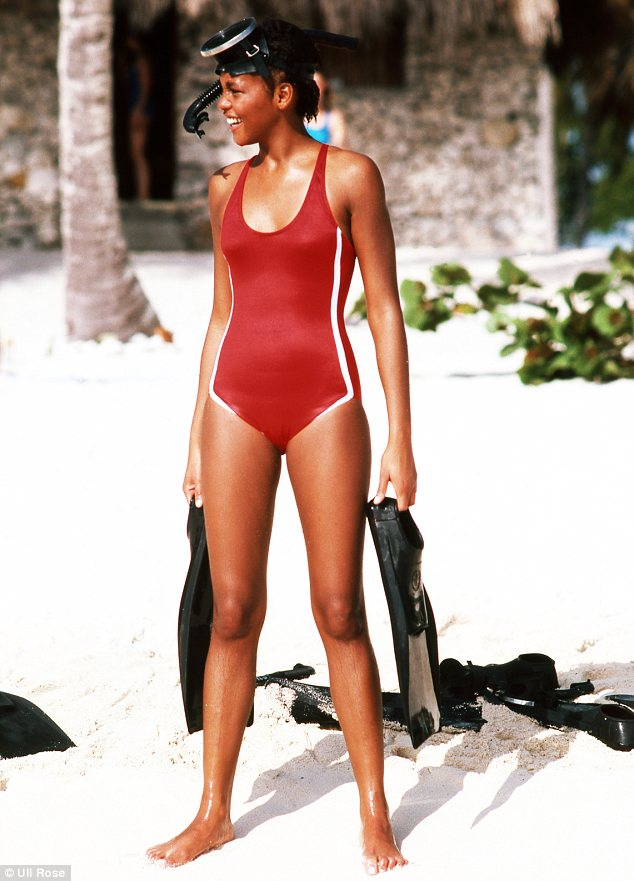 Whitney Houston sporting a red one-piece along with a snorkelling mask as she carries flippers before heading out into the surf
