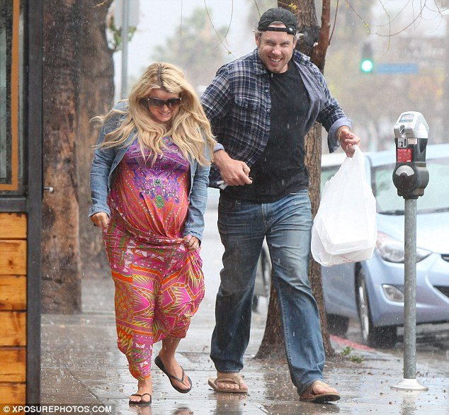 Heavily pregnant Jessica Simpson was caught in a downpour with fiancé Eric Johnson while leaving the Boneyard Bistro in LA