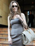 Angelina Jolie is getting used to wearing her huge engagement diamond as she headed to a meeting yesterday