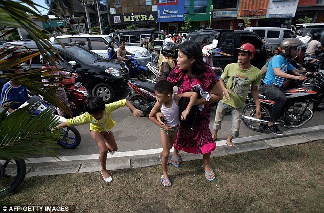 Tsunami alert caused panic among Indonesian people who fled buildings and made for high ground photo