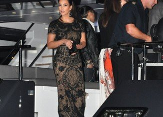 Kim Kardashian poured her ample curves into a stunning lace outfit which consisted of a crop top and matching maxi skirt