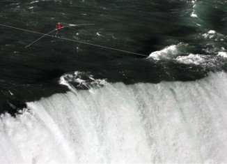 Nik Wallenda braved wind and heavy spray to make the 1,800 ft (550 m) walk from the US to Canada on a 2-inch (61 mm) wire