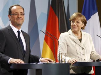 Angela Merkel and Francois Hollande are set to hold talks in Berlin on whether to give Greece more time to make the cuts required by its debt bailout