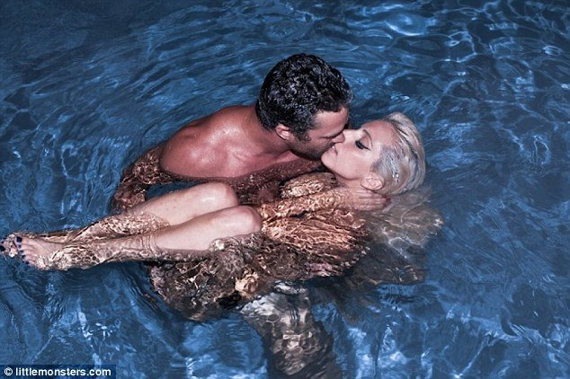 Lady Gaga appears to be skinny-dipping with her boyfriend Taylor Kinney as he embraces her for a passionate kiss in the water