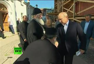 Vladimir Putin reacts awkwardly as a priest bows to kiss his hand during a visit to country's northern Valaam Island