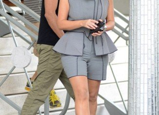 "Kim Kardashian covered her famously curvaceous figure in a grey sleeveless ""skorts-suit"" while shopping in Miami Beach"