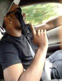 Nick Gordon is seen holding the firearm up to his face while driving a car using the other hand