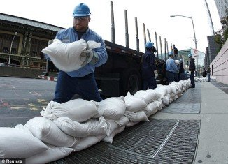 Con Edison workers prepare for Hurricane Sandy using sandbags to cover up power vaults in New York