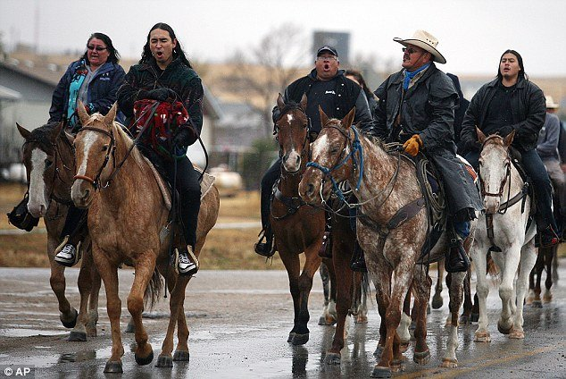 Family and friends of Russell Means sing as they ride horses down the Big Foot Trail during a 12 hour service in North Dakota on Wednesday
