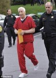 Flanked by sheriff's deputies, Jerry Sandusky's bullet-proof vest can visibly be seen under his jumpsuit