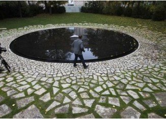 Roma Holocaust memorial is a circular pool of water with a small plinth in the middle in the Tiergarten park, near the Reichstag