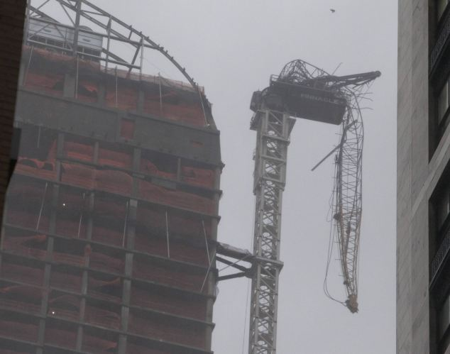 The storm engulfing New York has ripped a crane off the top of a 65-story luxury building and torn the face off an apartment in the West Village