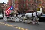A carriage drawn by white horses carried Hector Camacho's body around the streets of Spanish Harlem, taking the casket cover with a Puerto Rican flag to St. Cecilia's Catholic Church