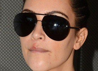 Kim Kardashian revealed a painful-looking large sore on her upper lip, along with blemishes on her chin as she flew into Miami on Sunday