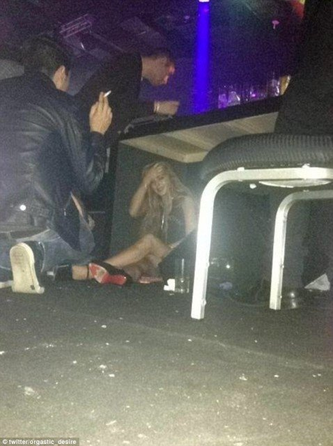 Lindsay Lohan was snapped sitting on a dirty floor under a table at a nightclub later in Sao Paulo to avoid taking pictures with fans