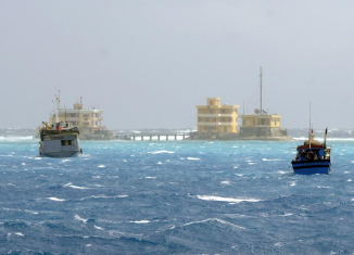 Vietnam has accused a Chinese vessel of firing on one of its fishing boats in disputed waters in the South China Sea, setting it alight