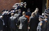 Firefighters honor guard salute as pallbearers carry the casket of Boston Marathon bomb victim Krystle Campbell into St Joseph's Church for her funeral in Medford