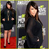 Kim Kardashian flattered her pregnant figure in a sexy black dress on the red carpet at the 2013 MTV Movie Awards