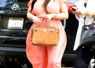 Kim Kardashian had another unflattering choice of maternity wear with a salmon pink dress that billowed dramatically at the hips as she attended church with her mother Kris Jenner