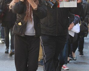 On her 27th birthday, Amanda Bynes was snapped taking a picture of paparazzi and hiding her face with a man in the background holding up a tabloid spread about her