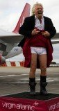 """Richard Branson lifted up his kilt to the watching crowd to reveal pants bearing the slogan """"stiff competition"""" as he stepped off the first Virgin plane at Edinburgh airport from Heathrow"""