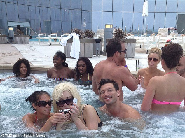 Amanda Bynes was pictured in a jacuzzi at the Revel Hotel where a few people gathered to get a photo as she wore her trademark blonde wig photo