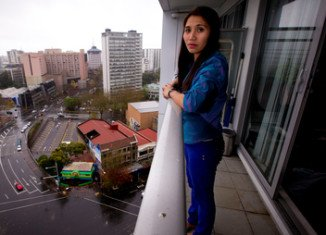 Geraldine Bautista on the 15th floor balcony from which she tried unsuccessfully to save Tom Stilwell who fell 13 floors outside the Volt apartment block in downtown