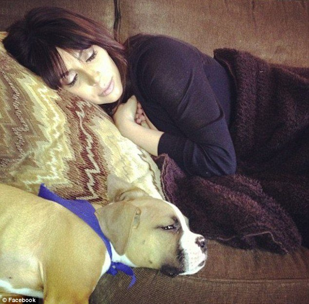 Kim Kardashian has shown up on Khloes Facebook page looking exhausted and enjoying a nap with boxer pup Bernard photo