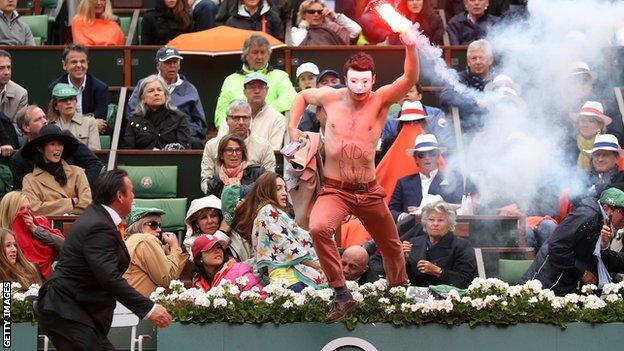 Masked protester waving a lit flare ran onto the court at the men's final of the French Open tennis in Paris
