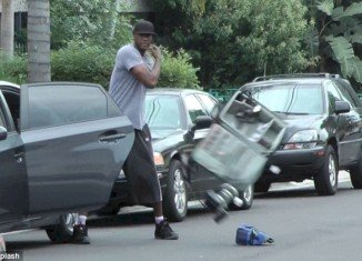 Lamar Odom lost his temper as he walked up to a photographer's car and threw all of his equipment out onto the street