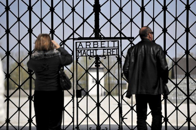 Angela Merkel has laid a wreath at the former Nazi concentration camp of Dachau, in the first such visit to the site by a German chancellor