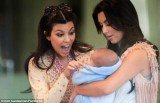 Kim Kardashian posted a Facebook picture of herself and sister Kourtney cooing over a new born baby