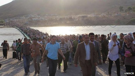 Thousands of Syrian refugees are pouring over the border into Iraqi Kurdistan photo